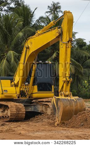 Yellow Excavator On A Construction Site Against Blue Sky. Heavy Industry. Close Up Details Of Indust