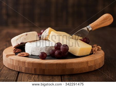 Selection Of Various Cheese On The Board And Grapes On Wooden Table Background. Blue Stilton, Red Le