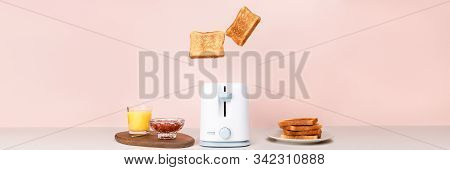 Toasted Bread Flew Out Of White Toaster. Near Glass Of Orange Juice, Bowl With Strawberry Jam And St