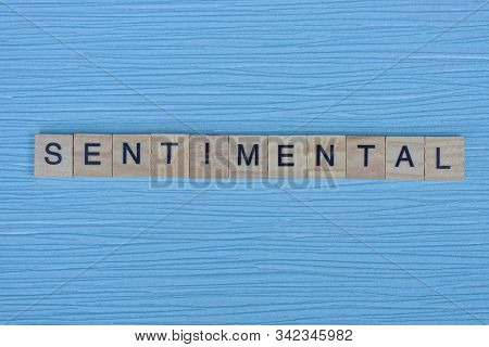 Word Sentimental From Small Wooden Letters On A Blue Table