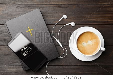 Bible, Phone, Cup Of Coffee And Earphones On Wooden Background, Flat Lay. Religious Audiobook