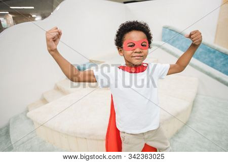 Cute little boy of African ethnicity wearing red mantle of super hero and white casualwear showing his power