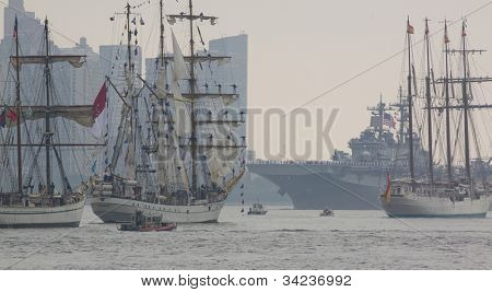 HOBOKEN, NJ - MAY 23: A battleship and several tall ships pass on the Hudson River near Manhattan during the Parade of Sails on May 23, 2012 in Hoboken, NJ. The parade marks the start of Fleet Week.