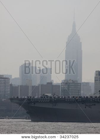 HOBOKEN, NJ - MAY 23: The USS Wasp (LHD 1) passes the Empire State Building on the Hudson River during the Parade of Sails on May 23, 2012 in Hoboken, NJ. The parade marks the start of Fleet Week.