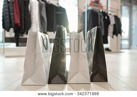 Row of black and white paperbags standing on the floor of boutique on background of new collection of clothes on racks