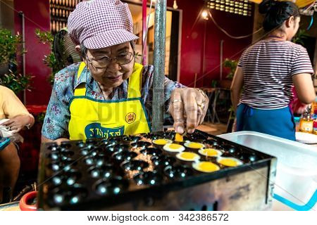 Krabi Town, Thailand - November 23 2019: An Elderly Thai Woman Prepared Fried Eggs Off Bird  In Krab