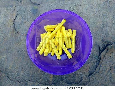 Some Eatable Yellow Food Put In A Plastic Bowl On Stone Background