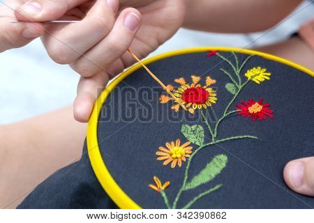 Women's Hand Embroidery In A Hoop, A Woman Embroider A Pattern On Dark Material. Close-up. The Conce