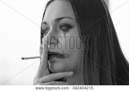 Young Beautiful Woman With Greased Make Up, Smoking In Stress Or Melancholy Mood. Domestic Violence