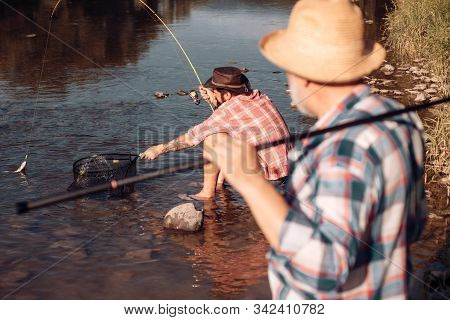 Bearded Men Catching Fish. Lear Water River. Hobby Sport Activity. Elegant Bearded Man And Brutal Hi