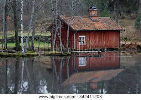 Small Red Old Wooden Wash-house Near The Ice Covered Lake.