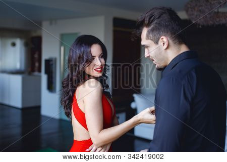 Sexy Woman In Red Flirting Seducing Younger Man Indoors