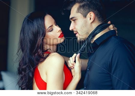 Tempting Milf Woman In Red Holding Young Lover By Tie, Seduction