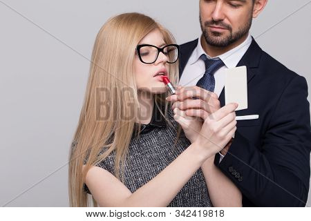 Young Femme Fatale Woman Applying Red Lipstick With Mans Helping Hand