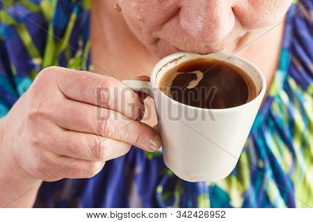 Elderly Woman Drinking Hot Drink At Home. Senior Pensioner Female Holding Cup Of Coffee In Their Han