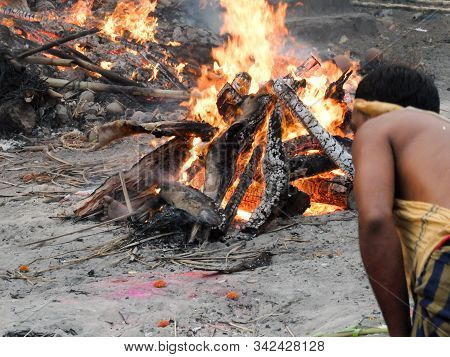 Puri,odisha/india-march 12 2018:a Worker Tends The Pyre Of A Hindu Person At Swargadwar Crematorium