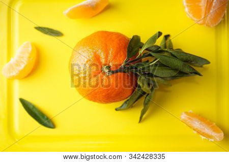 Flat Lay Mandarin With A Green Branch And Mandarin Slices On A Yellow Kitchen Board.