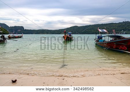 Traditional Wooden Longtail Boats Parked At A Beach In Phi Phi Island. Clear Water And Clean Beach.