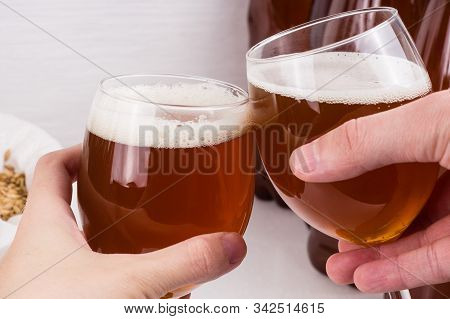 Homemade Craft Beer  In Wineglass In Two Hands On White Background.  Ale Or Lager From Pilsner Malt