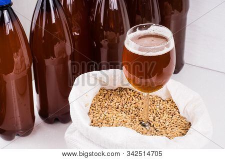 Homemade Beer From A Plastic Bottle Is Poured Into A Glass Against The Background Of Other Beer Bott