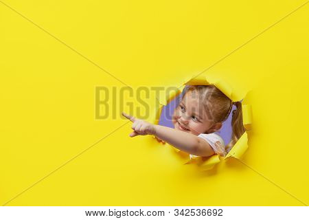 Little Surprised Child Looking, Peeping Through The Bright Yellow Paper Hole. Advertise Childrens Go