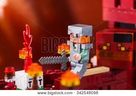 Kiev, Ukraine - December 29, 2019: Minifigure Alex With Sword Running Away From The Magma Cube. Char