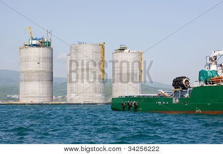 Ocean tug towing the base offshore oil drilling platform. Sea of Japan. Russian coast.