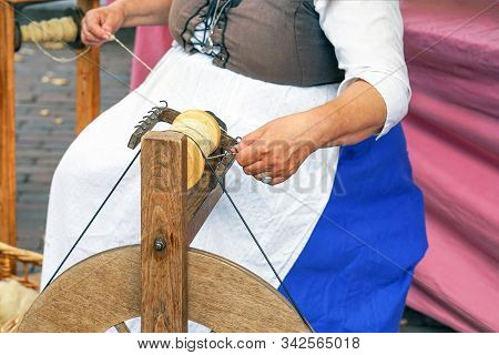 Craftswoman Using An Old Spinning Wheel To Turn Wool Into Yarn. Hands Of A Woman Demonstrating Tradi