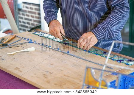 A Man Artist Collects Small Squares Of Glass Mosaic. Painter Man Makes Stained Glass. Close-up Of A
