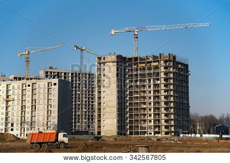 Hydraulic luffing jib tower cranes and workers being poured concrete into foundation. Cement pouring into formwork of building at construction site. Tower cranes constructing a new residential build poster