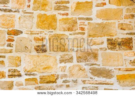 Surface With Asymmetrical Stones. Wall Of A Medieval Fortress. Wall With Light Colored Stones Of Var