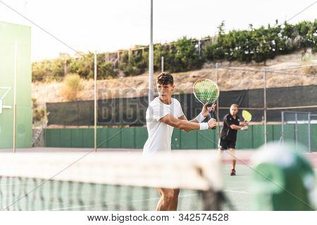 Two Men Playing Tennis As A Team Outdoors.