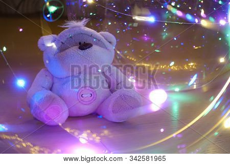 A Toy Teddy Bear Surrounded By Colored Lights. Abstract Fairytale Magic Background.