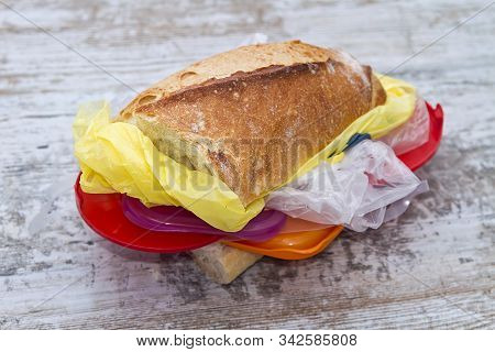 A Metaphoric Image Of A Sandwich Filled With Plastic Food