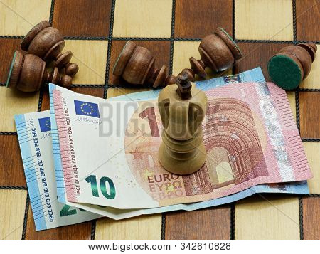 Money Rules Concept: King Chess Piece Standing On Euro Banknotes With Defeated Lying Pawns On A Ches
