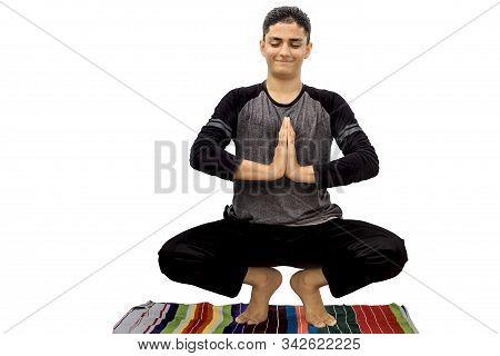 Full-length Shot Of Male Teenager Doing Malsasana Yoga Pose Isolated. Isolated Shot Of Male Teenager