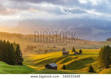 Beautiful Sun Rise View Of Local Huts And Shack In Golden Grass Meadow In Alpe Di Siusi In Cloudy Da