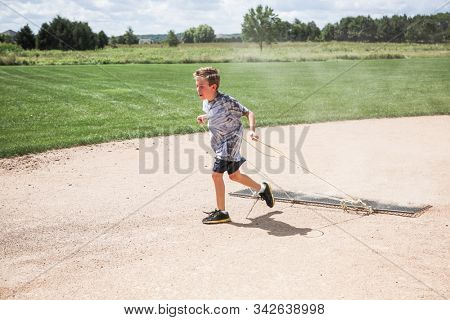 Young boy pulling an infield drag grooming it for a baseball game