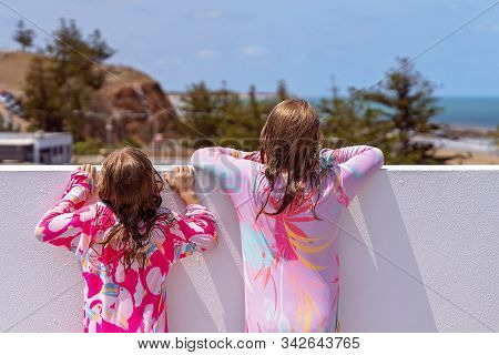 Two Young Blond Sisters Fresh Out Of The Pool And Dripping Wet, Standing On Tiptoes Looking Over A W