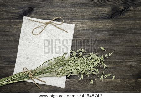 Small Linen Bag Knotted With Jute Twine And Green Ears Of Oats On A Dark Wooden Background. The Conc