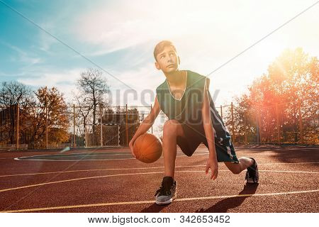 Sports And Basketball. A Young Teenager In A Green Tracksuit Playing Basketball, Leading The Ball. B
