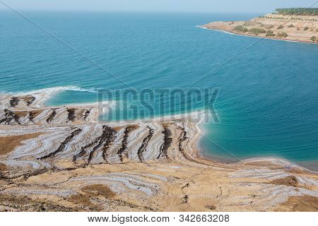 View of Dead Sea coastline at sunset time in Jordan. Salt crystals at sunset. Dead sea landscape wit