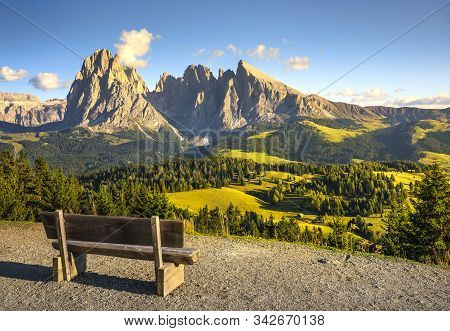 Alpe Di Siusi Or Seiser Alm And A Wooden Bench, Dolomites Alps Sassolungo And Sassopiatto Mountains,