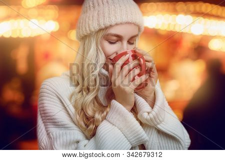 Young Woman Enjoying A Mug Of Hot Coffee In Winter Cupping It In Her Hands As She Drinks With A Blis