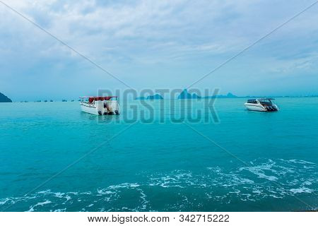 Speed Boat With Outboard Boat Motor And Dark Blue Sunroof Anchored In Local Harbor Surrounded With C
