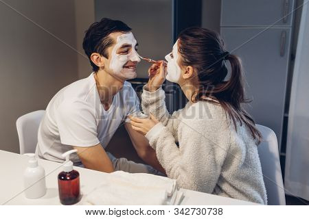 Woman Applying Clay Mask On Her Husbands Face. Young Loving Couple Taking Care Of Skin At Home. Heal