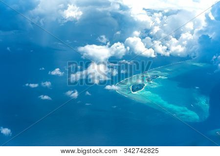 Aerial View Of Maldives Island Beautiful Blue Ocean With Clouds And Atolls Famous Tourist Place To V