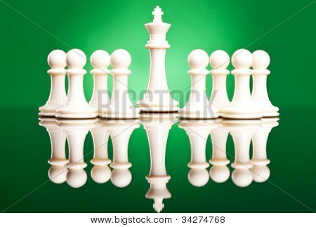white pawns protecting their leader, the white king - chess pieces on green background