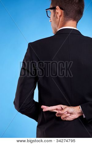 business man with fingers crossed behind back isolated over white background