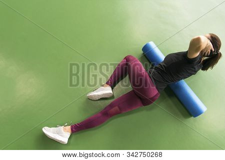 Woman Doing Foam Roller Exercise On A Floor In Gym